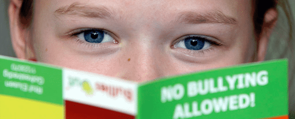 Kid reading no bullying pamphlet