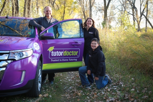 Rachel and Jeff Jensen with Son Posing with Tutor Doctor Car